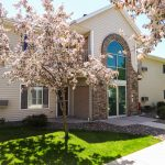 apartment-building-entry-door-with-green-grass-and-flowering-trees-medford-wi